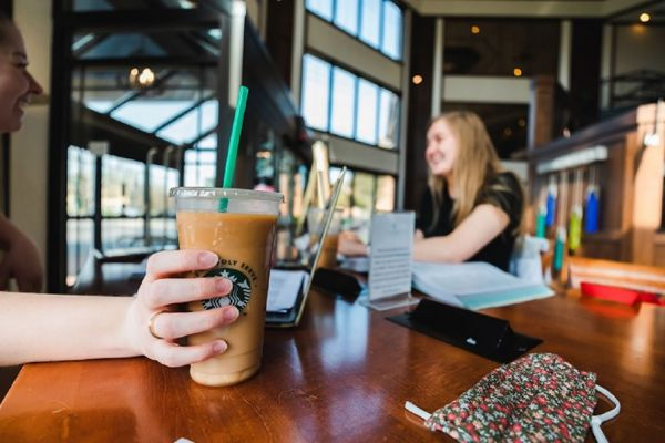 Person at a table at InnJoy Cafe holding a Starbucks beverage.