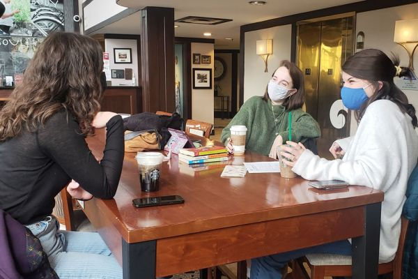 Three friends in face masks sitting at a table at InnJoy Cafe enjoying Starbucks beverages.