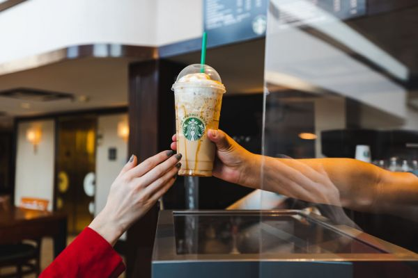 Starbucks beverage being handed over the display window from a barista to a customer.