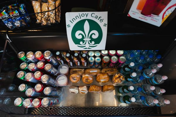 The cooler at InnJoy Cafe, containing breakfast sandwiches, bottled water, and other various drinks.
