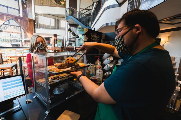 Barista using tongs to grab a muffin for a customer while wearing a face mask at InnJoy Cafe.